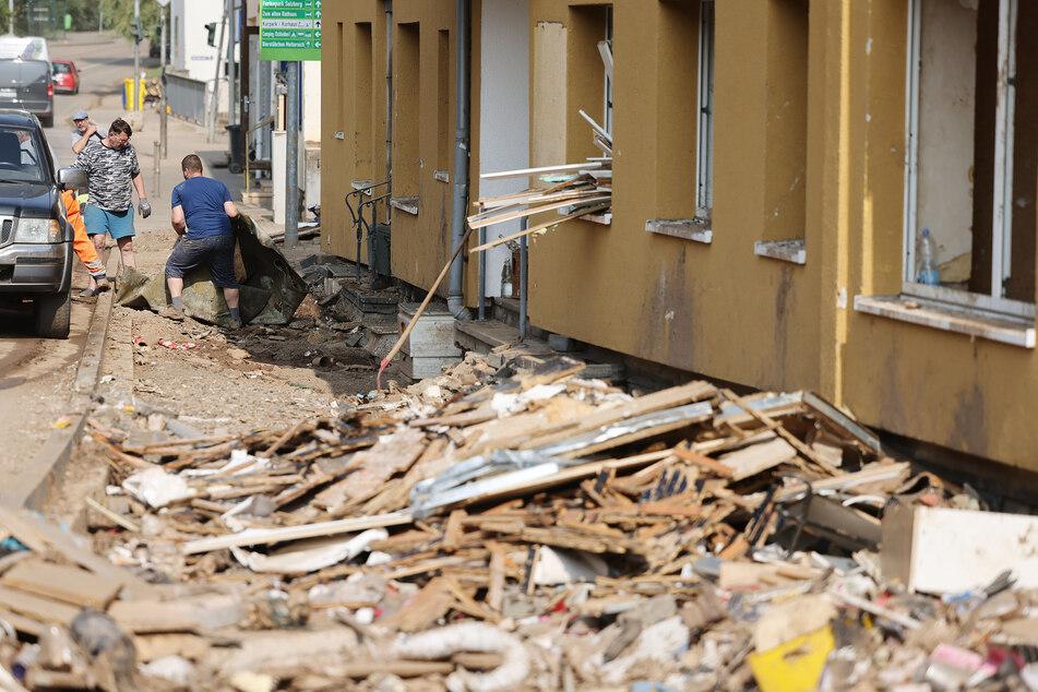 In Gemünd (Eifel) räumten Menschen Ende Juli, zwei Wochen nach der Flut, Schutt und Trümmer aus ihren zerstörten Häusern. Das Hochwasser hatte Milliardenschäden angerichtet, jetzt können Anträge auf Wiederaufbauhilfe gestellt werden.