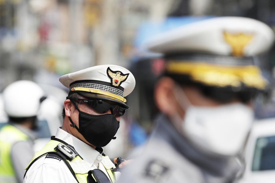 Polizisten mit Schutzmasken stehen Wache.