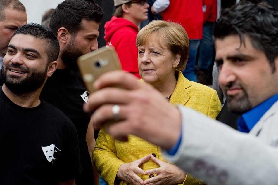 Angela Merkel wird 2015 von Flüchtlingen, die in Deutschland aufgenommen wurden, fotografiert.
