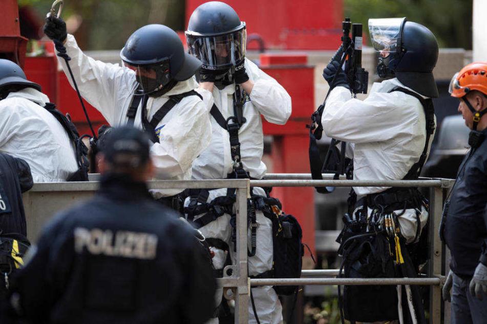 Polizisten im Hambacher Forst tragen Schutzanzüge.