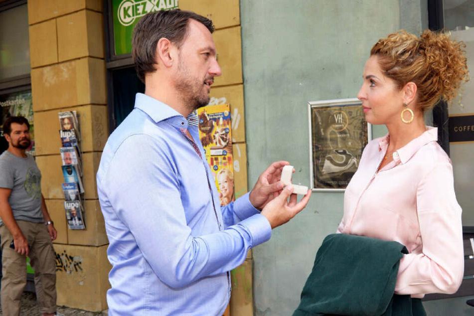 Leon beobachtet, wie Robert Nina einen Ring überreicht.