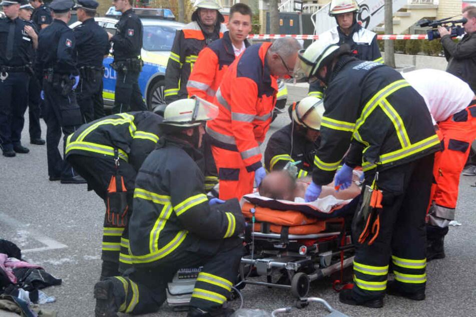 Feuerwehrleute und Sanitäter versorgen den verletzten Mann in der Nähe des Einkaufszentrums Quarree.