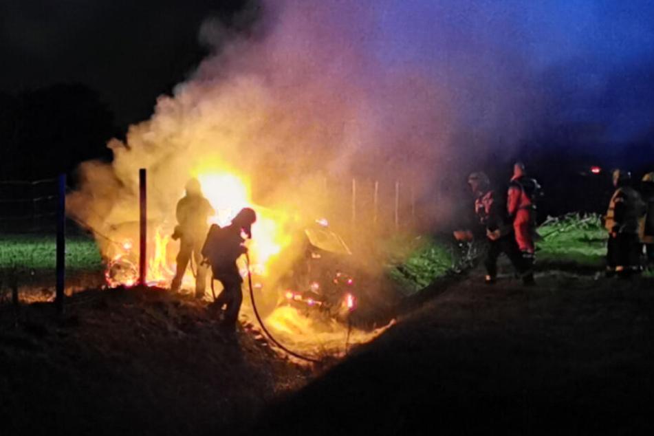 Die Feuerwehr löscht den brennenden SUV.