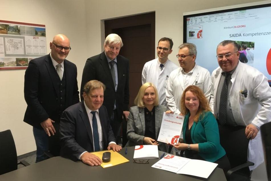 Freuen sich auf die gemeinsame Zusammenarbeit: Bürgermeister T.Fabian, Klinik-Chefin Dr. I. Minde, S. Schwarz (sitzend) sowie L. Kindermann, Dr. Ch. Geyer, Prof. T. Kremer, Prof. W. Köhler und Prof. A. Hamza (stehend).