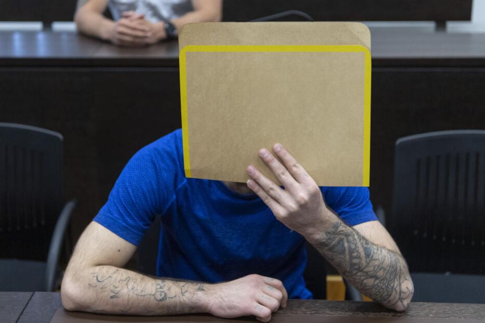 Mit einer Aktenmappe verdeckt der Angeklagte Ali Bashar beim Betreten des Sicherheitssaals des Landgerichts sein Gesicht.
