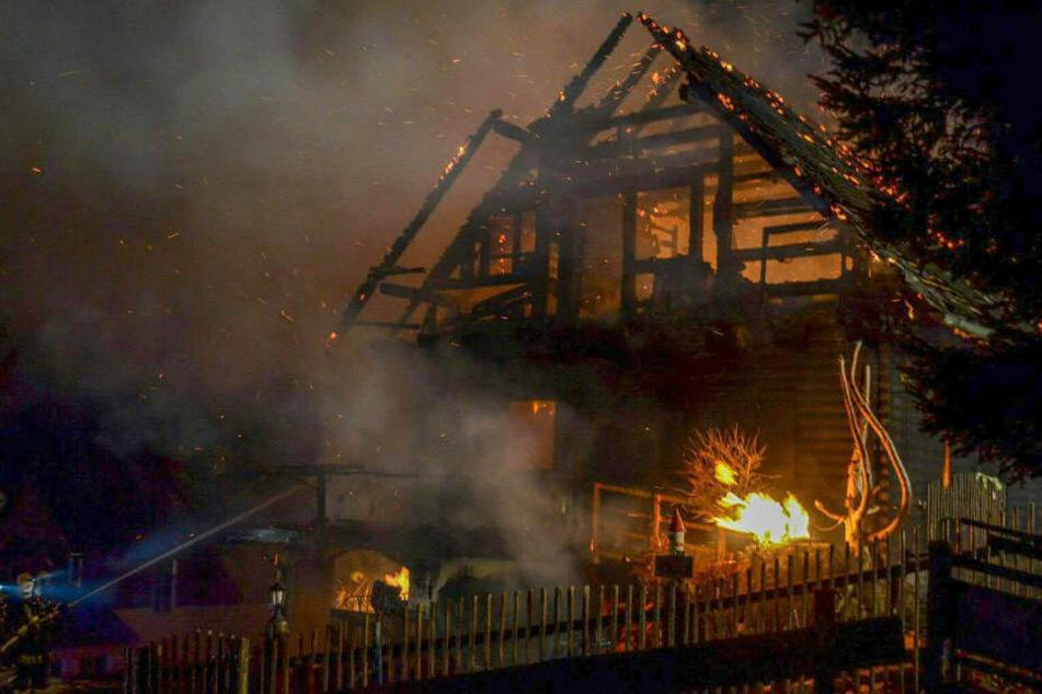 Einsatzkräfte der Feuerwehr stehen vor einem Einfamilienhaus und versuchen, einen Brand zu löschen.