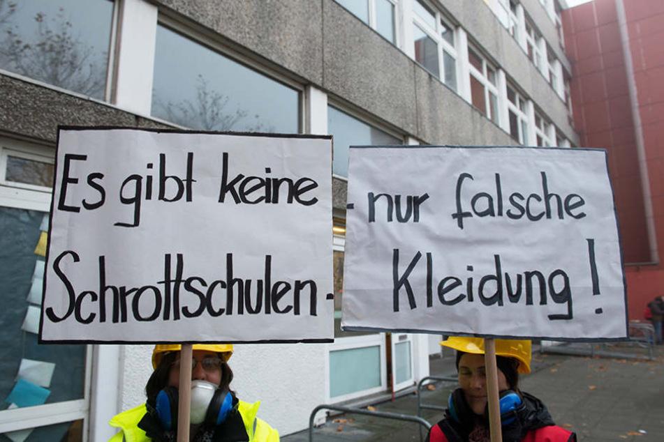 Zwei Demonstranten halten vor der Carlo-Schmid-Oberschule in Spandau Plakate in den Händen.