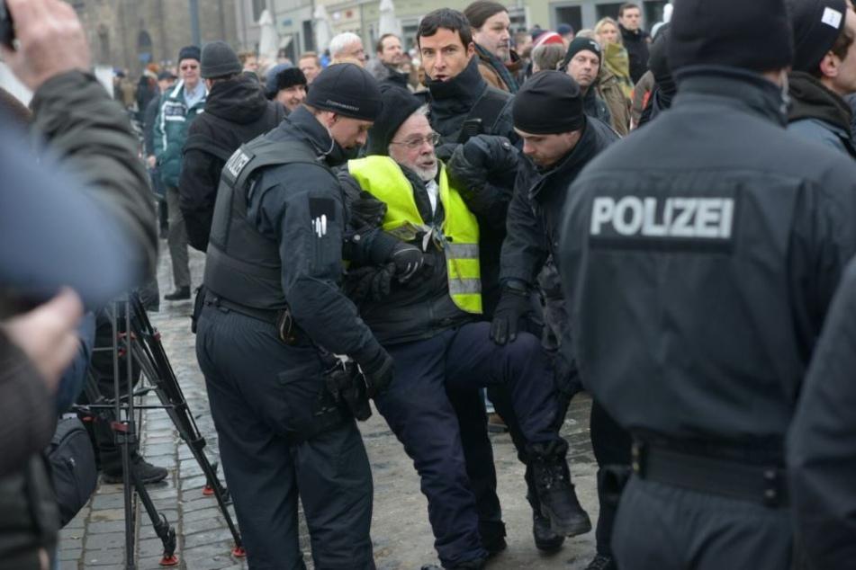 Ein Mann wird von der Polizei weggebracht.