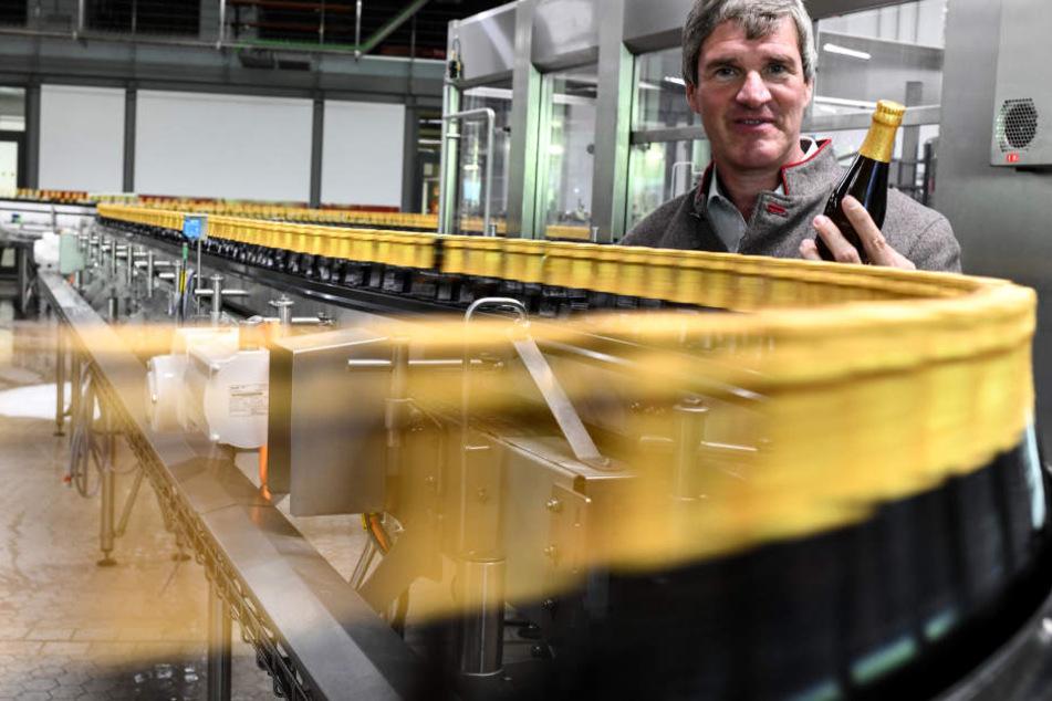 """Vorstand Christian Rasch von der Badischen Staatsbrauerei Rothaus steht in der Abfüllanlage und hat einer Flasche """"Tannenzäpfle"""" in der Hand."""