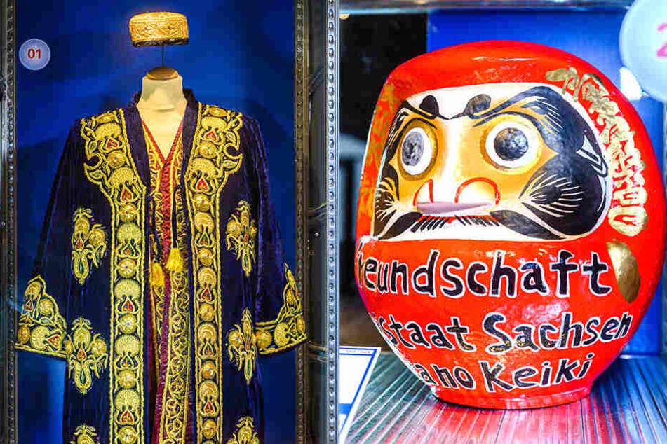 """Diese Nationaltracht (l.) aus Samt schenkte Usbekistans Staatspräsident 2001 Kurt Biedenkopf beim Besuch in Dresden. 2007 bekam MP Milbradt diesen Glücksbringer (""""Daruma"""") von einer japanischen Firma (rechts)."""