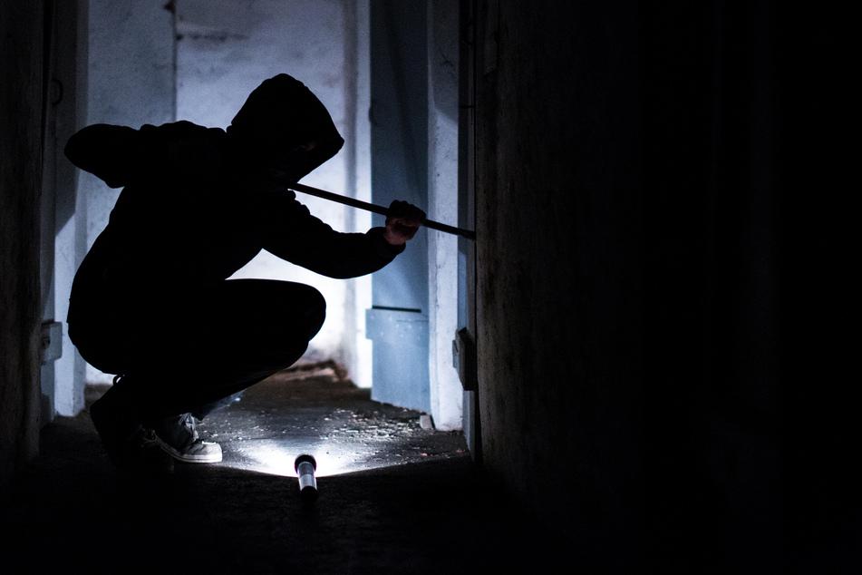 Ein fiktiver Einbrecher hebelt mit einem Brecheisen eine Tür im Keller eines Wohnhauses auf (gestellte Szene).