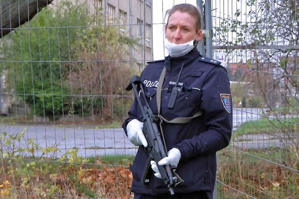 Eine bewaffnete Polizistin sichert die Durchsuchungsmaßnahmen.
