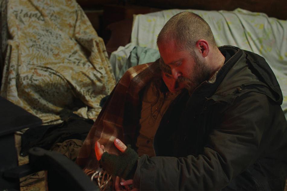 Tom (l., Thomasin McKenzie) und Will (r., Ben Foster) wärmen sich in einem Waldhaus am Kamin auf.