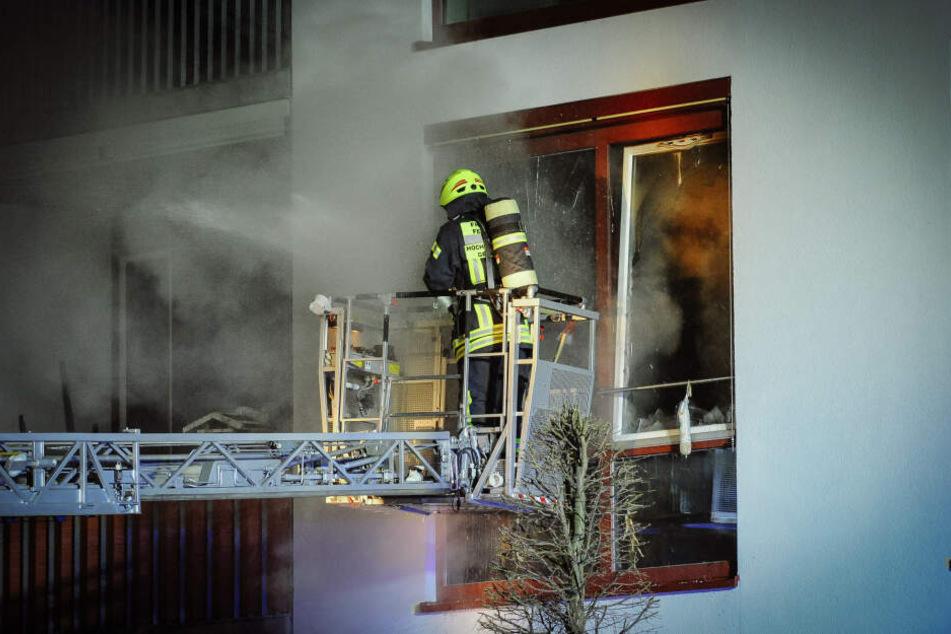 Ein Feuerwehrmann kämpft auf einer Drehleiter gegen die Flammen.