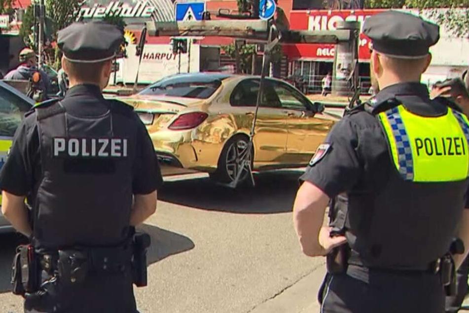 Beamte stehen hinter dem sichergestellten Fahrzeug auf der Hamburger Reeperbahn.