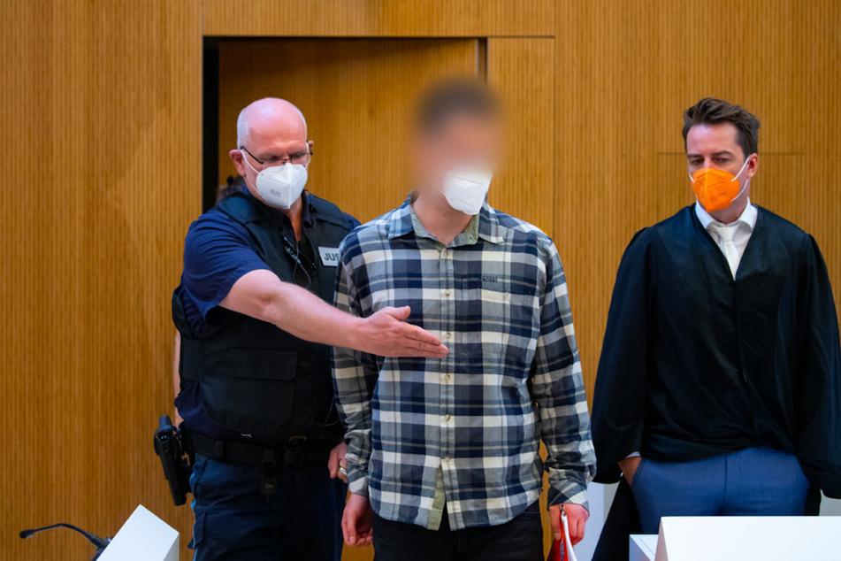 Einer von zwei wegen Mordes angeklagten Männer (M.) wird vor Beginn der Verhandlung in den Sitzungssaal geführt. Rechts steht sein Anwalt Alexander Stevens.