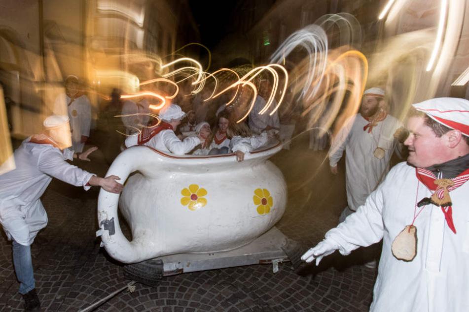 Mit Nachthemden bekleidete Mädchen werden in der Innenstadt von Radolfzell beim Hemdglonkerumzug in einem riesigen Nachttopf gedreht. (Archivbild)