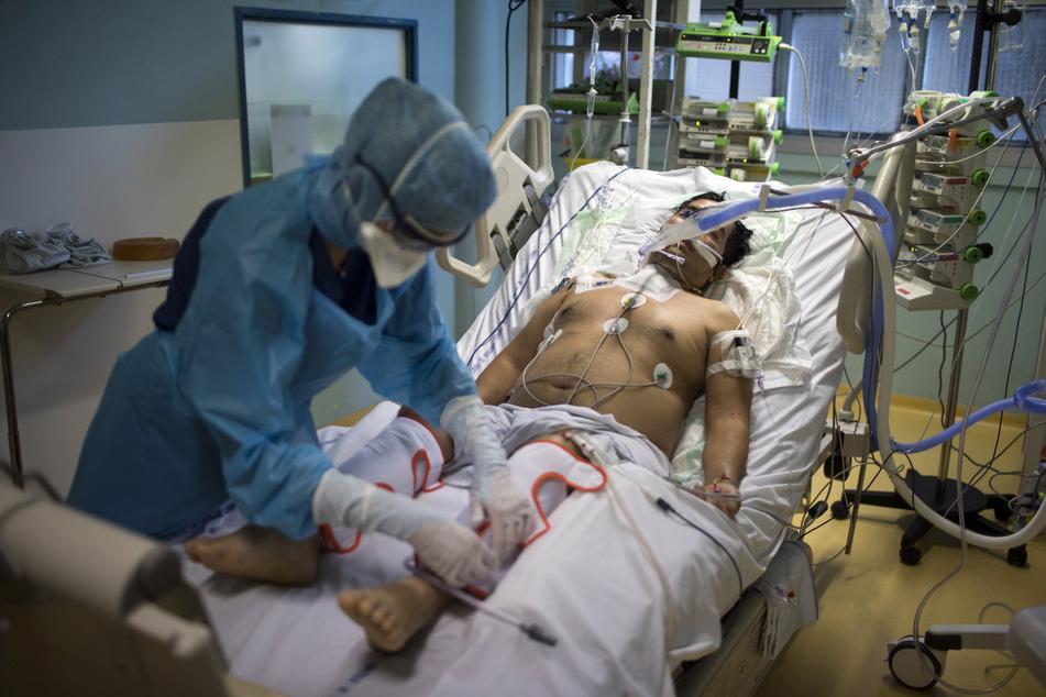 Eine Krankenschwester in Schutzkleidung untersucht einen coronainfizierten Patienten in der Intensivstation des Joseph-Imbert-Krankenhauses.