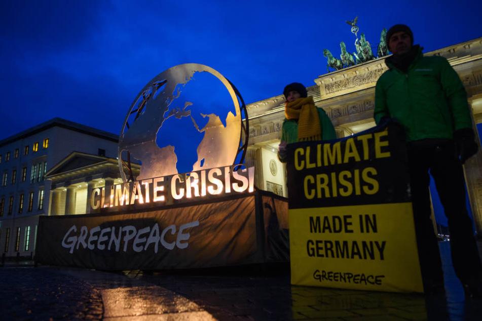 Greenpeace-Aktivisten haben am Dienstagmorgen mit einer brennenden Weltkugel vor dem Brandenburger Tor protestiert.