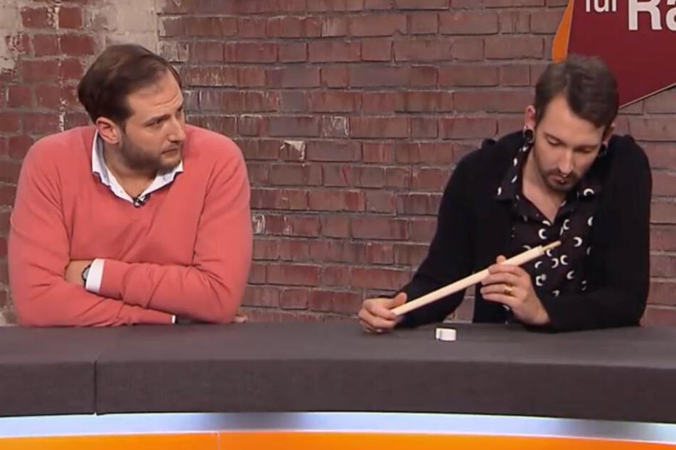 Fabian Kahl (r.) inspiziert den Flanierstock aus Elfenbein, Julian Schmitz-Avira schaut interessiert zu.