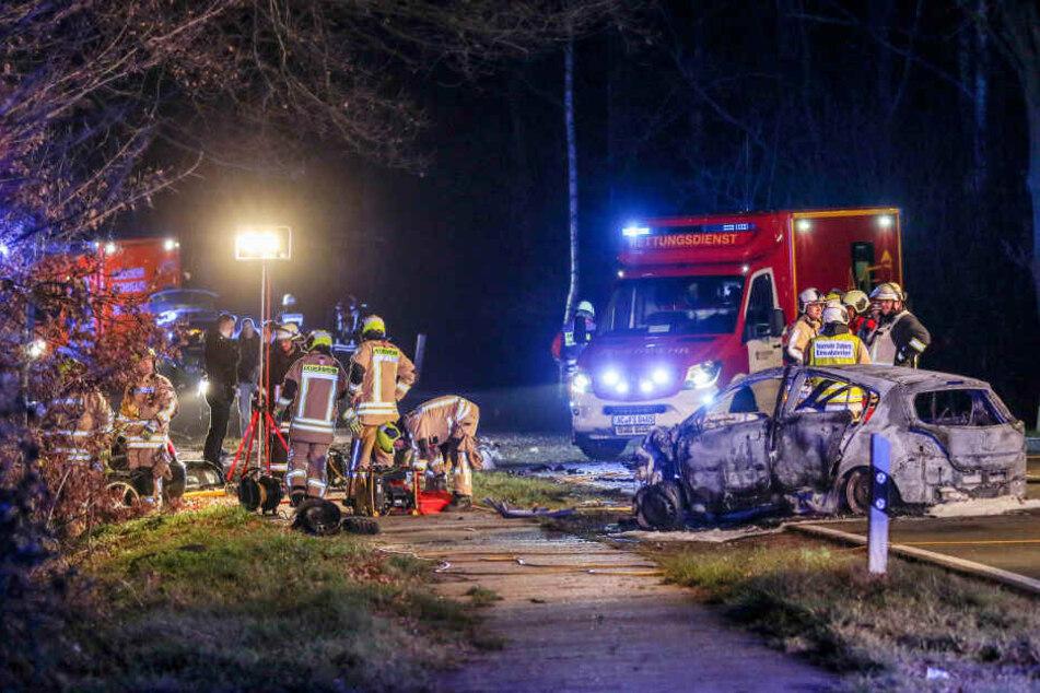 22.12.2018, Nordrhein-Westfalen, Stolberg: Feuerwehrleute stehen an zwei Fahrzeugen, die frontal zusammengestoßen waren.
