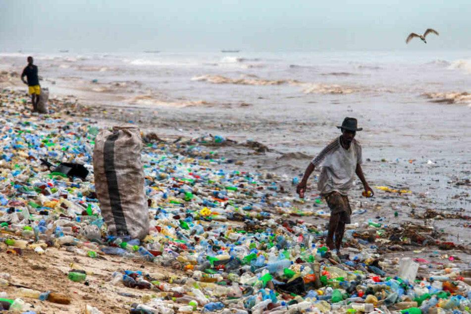 Ein Mann läuft durch den völlig verschmutzten Kohle Gono Strand in Ghana.