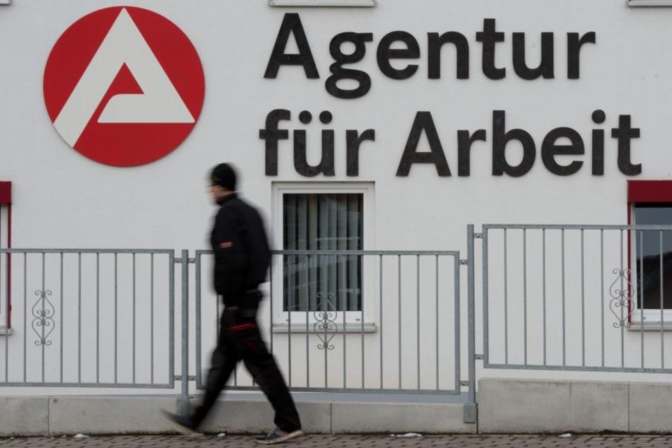 Ein Passant geht an dem Logo der Agentur für Arbeit vorbei.