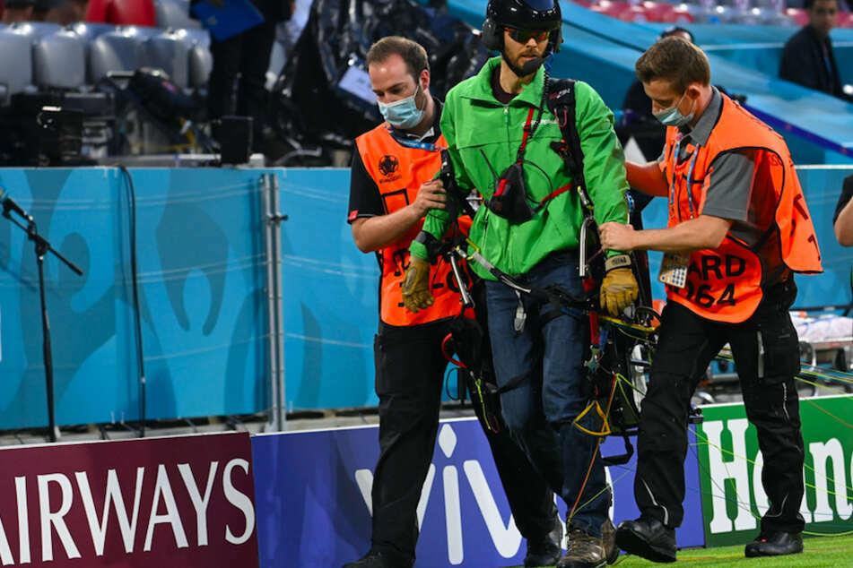 Der Greenpeace-Aktivist wird vom Spielfeld geführt.