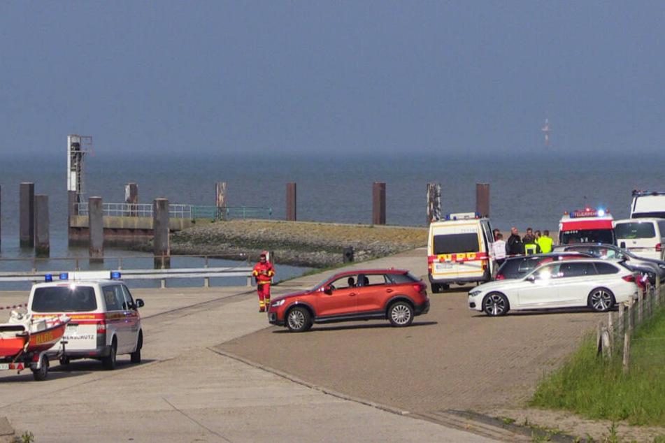 Helfer der Deutschen Lebens-Rettungs-Gesellschaft stehen bei einer Suchaktion auf einem Parkplatz neben der Nordsee.