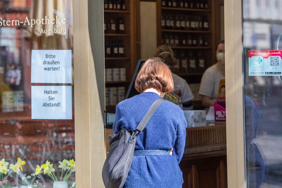 Vor der Tür einer Apotheke wartet eine Frau. Die Apotheke darf nur noch einzeln betreten werden.