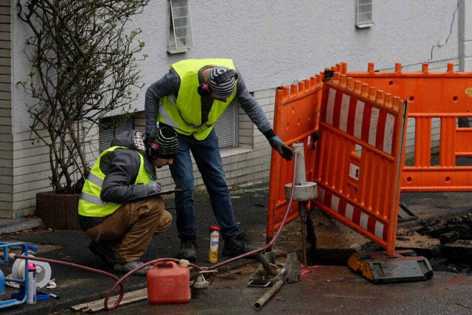 Zwei Männer untersuchen vor einem vom Einsturz bedrohtem Haus den Untergrund.