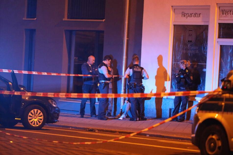 Eine Augenzeugin der Schießerei sitzt geschockt auf dem Bürgersteig. Polizisten stehen vor ihr.