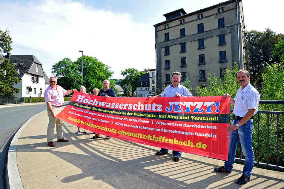 Protest für mehr Hochwasserschutz: Mit Bannern fordern Anwohner den Bau von  Mauern und eines Rückhaltebeckens.
