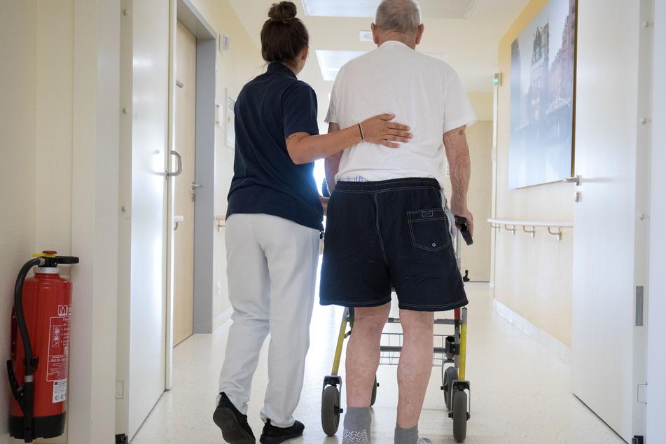 Eine Krankenschwester begleitet einen älteren Mann mit Rollator auf dem Weg zu seinem Zimmer.