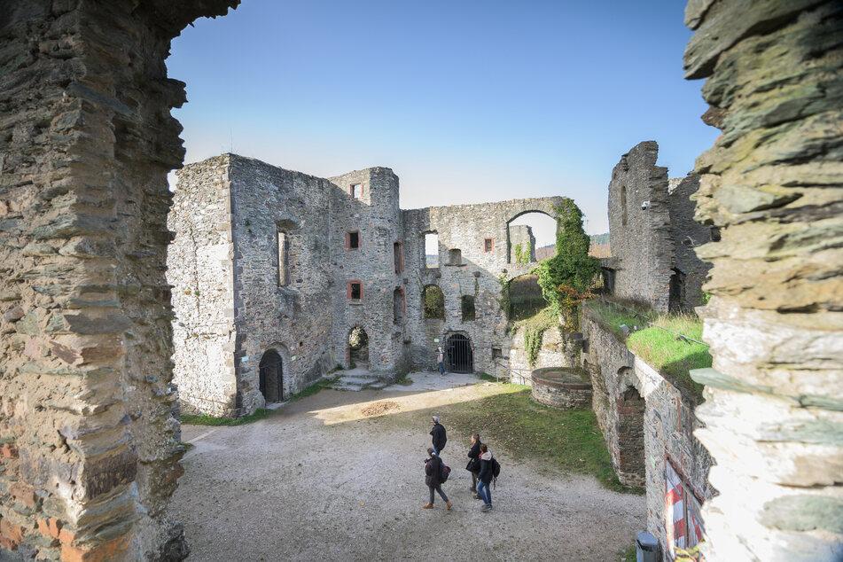 Menschen gehen durch die Burgruine Königstein in Hessen.