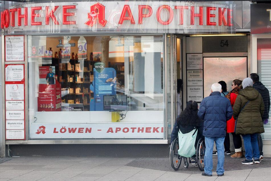Vor der Eingangstüre einer Apotheke hat sich eine Menschenschlange gebildet, weil nur noch jeweils ein Kunde die Apotheke betreten darf.