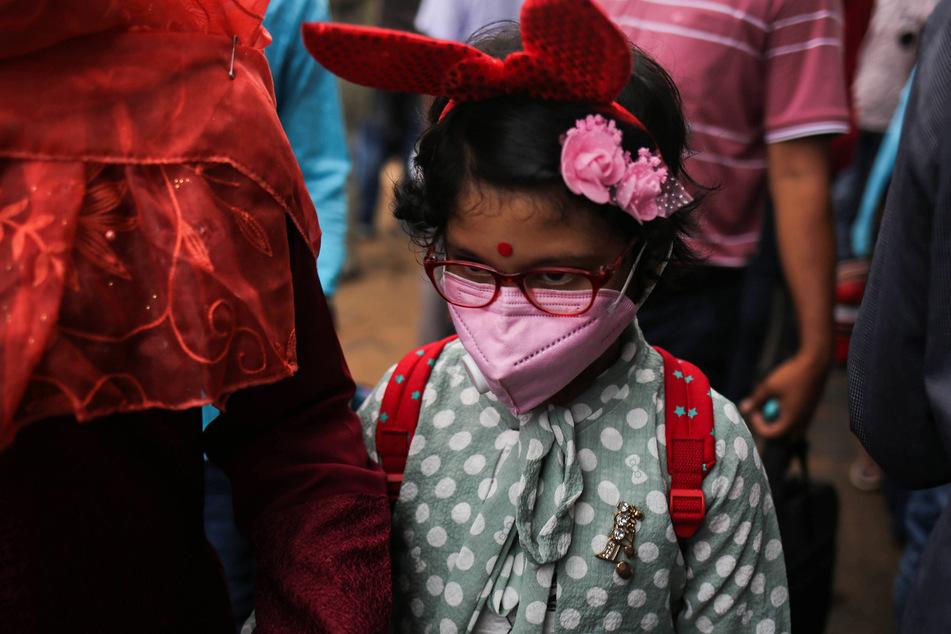 Ein Mädchen trägt eine Maske. Auch Kinder können sich mit dem Coronavirus infizieren.