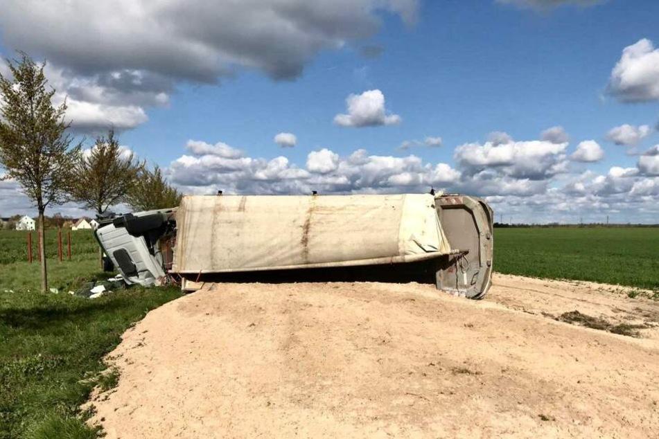 Ein mit Sand beladener Lkw ist auf einer Ortsverbindung in Brandenburg umgekippt.