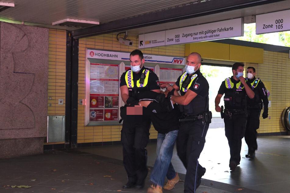 Die Polizei führt den Portemonnaie-Dieb ab.