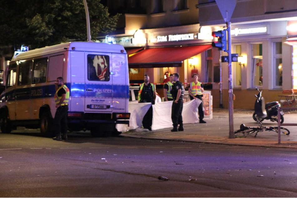 Polizeibeamte verdecken mit Tüchern die Sicht auf die verunglückte Frau.
