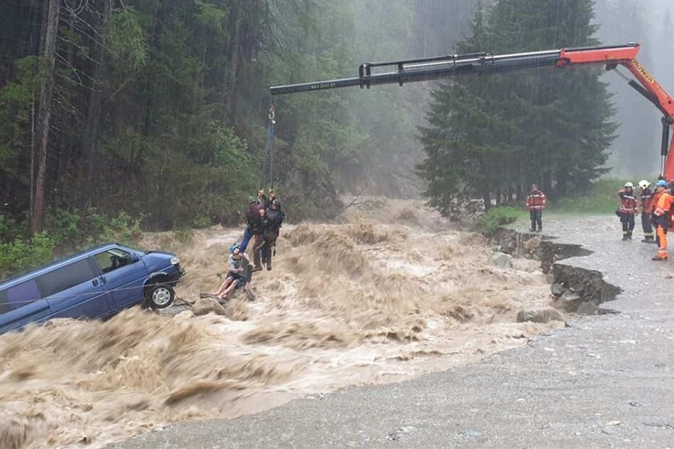 Rettungskräfte heben mit einem Kranfahrzeug zwei deutsche Touristen aus dem Auto, das vom reißenden Hüscherabach mitgerissen wurde.
