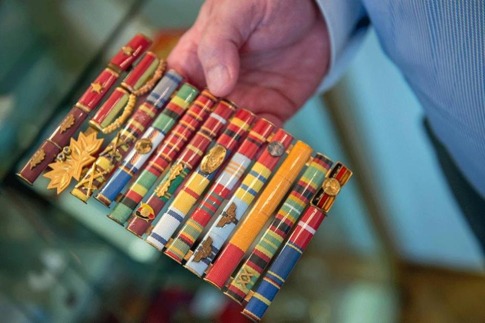 Ein Auktionator zeigt die Orden von A. Schalck-Golodkowski.