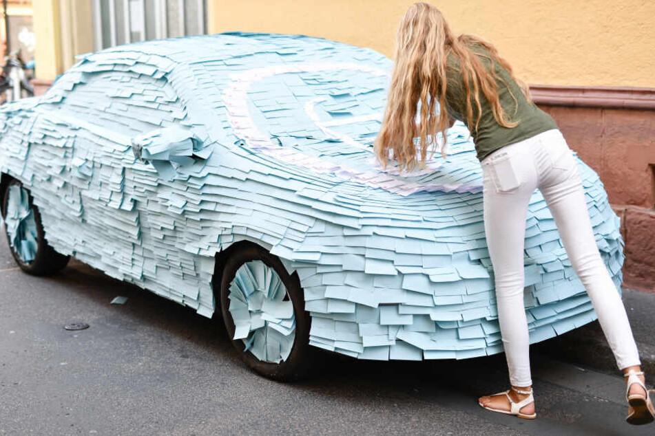 Eine Mitarbeitern der Initiative gegen Falschparken hüllt ein Auto mit Post-it-Zetteln ein. Die Stadt Heidelberg hatte das Fahrzeug extra für die Aktion dort abgestellt. (Archivbild)