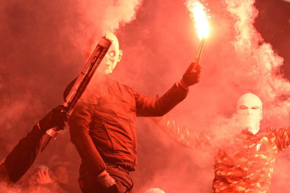 Mit Masken und vermummt halten Fans Pyro-Technik hoch.