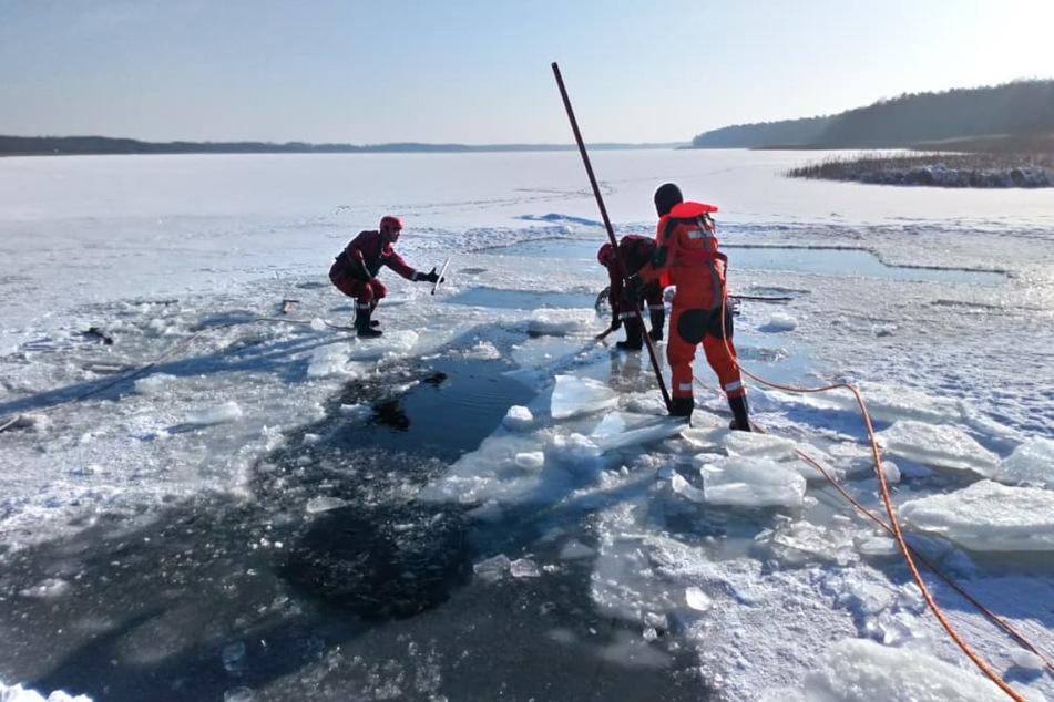 Die Kameraden der Feuerwehr schlugen weitere Löcher in das Eis auf dem See, um den Mann zu finden.