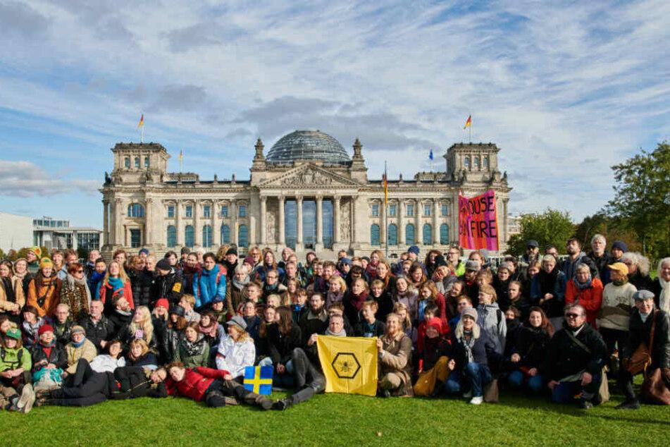 Eine schwedische Gruppe der Klimaschutzbewegung Extinction Rebellion platziert sich auf der Wiese vor dem Reichstag.