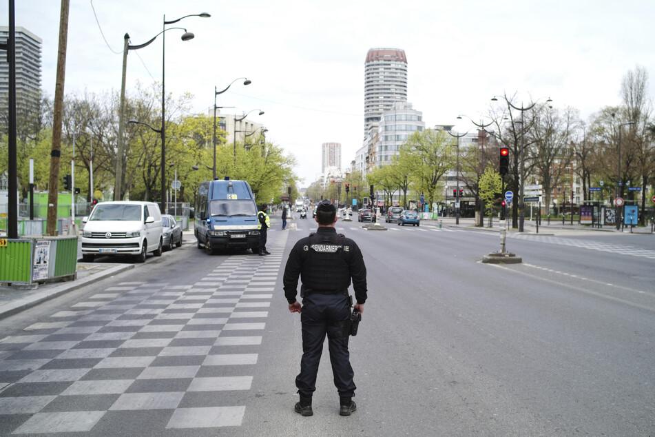 Ein Polizeibeamter patrouilliert an einem Straßen-Kontrollpunkt, um sicherzustellen, dass Personen ohne Sondergenehmigung den Kontrollpunkt nicht passieren. In Frankreich gelten landesweit strenge Ausgangs- und Transportbeschränkungen.