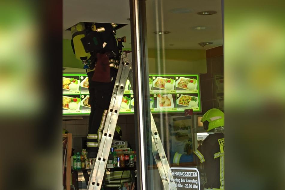 Die Feuerwehr prüft aktuell in einem Imbiss neben dem Bäcker verschiedene Kabel unterhalb der Decke.