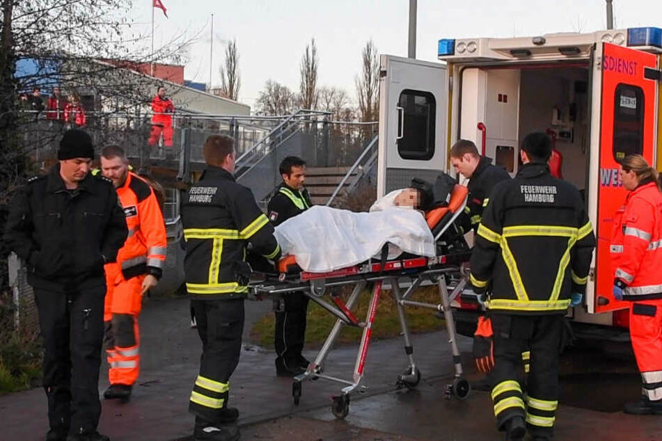 Der Verletzte wird in einen Rettungswagen geschoben und in eine Klinik gebracht.