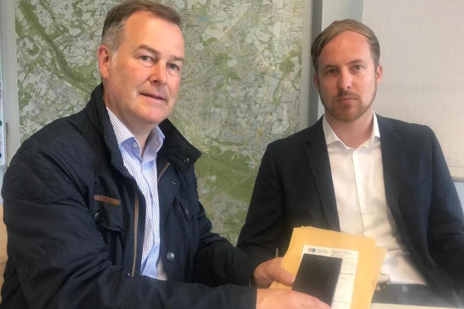Henning Stiegmann vom Staatsschutz Bielefeld (l.) und Staatsanwalt Christoph Hebbecker präsentieren das sichergestellte Smartphone.